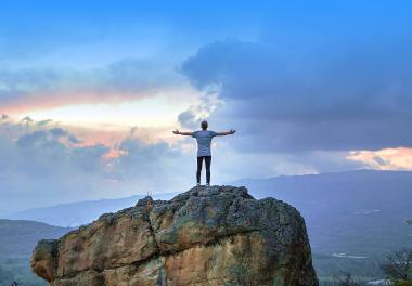 Guy with open arms on a mountain